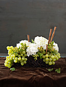 A homemade table centre made with white hydrangeas, green grapes and cinnamon sticks