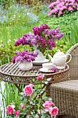 Fliedersträuße auf Tisch im Garten