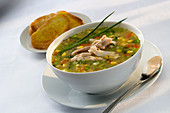 A bowl of Chicken and Vegetable Soup garnished with chives