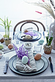 Table set for Easter in natural style with eggs and dyed grasses