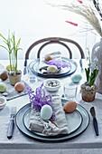 Natürlich gedeckter Ostertisch mit Eiern und gefärbten Gräsern