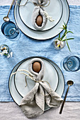 Easter bunnies made from eggs wrapped in napkins on table set in blue