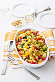 Pasta salad with blanches vegetables, cheese and roasted pine nuts