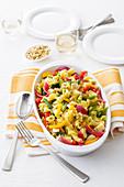 Nudelsalat mit blanchiertem Gemüse, Käse und gerösteten Pinienkernen