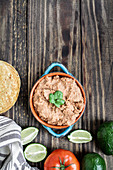 Refried beans with fried corn tortillas, avocados, tomatoes and fresh limes