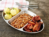 Brown beans with fried bacon and boiled potatoes