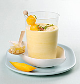 Yoghurt and mango smoothie with a mango skewer and pistachio nuts
