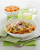 Penne pasta with spring onions, bacon and melon