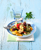 Warm vegetables salad with fresh herbs and olives