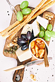 Cheese platter with apple chutney, nuts, capers, grapes and breadsticks