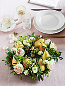 An autumnal wreath with pears and roses as a table centre