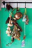 Knoblauch, getrocknete Kräuter und Küchenutensilien auf Hakenleiste