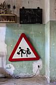 Verkehrsschild unter Kreidetafel an Wand mit abgeblätterter Farbe