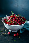Freshly picked sour cherries in a porcelain sieve