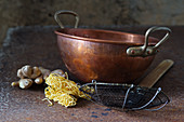 Asian still life with a copper bowl, sieve spoon, egg noodles and ginger