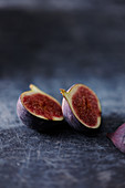 Two fig halves on a gray background