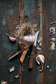 A bulb of garlic with a peeling knife on a vintage wooden surface