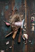 Eine Knoblauchknolle mit Schälmesser auf Vintage-Holzuntergrund