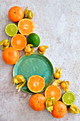 Citruses and physalis arranged on a light background
