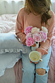 Woman is holding an empty coffee cup in her hands and a bouquet of peonies