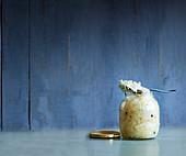 Sauerkraut im Schraubglas vor farbigem Hintergrund