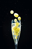 Grapes falling in glass of champagne with splash isolated on black background
