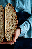 Woman in apron holding slice homemade sourdough bread