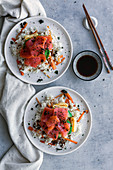 Sliced salmon on white rice with vegetables in plate and wooden chopsticks on table