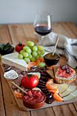 Vorspeisenplatte mit Salami, Käse, Obst, Gemüse, Brot und Wein
