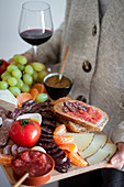 Waiter carrying wooden tray with sliced of meat vegetables fruits and glass of red wine