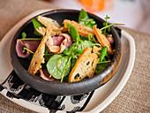 Pink roast beef with green salad and crusty bread in black stylish bowl on table