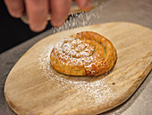 Chef sprinkling fresh baked Ensaimada with powdered sugar on wooden plate