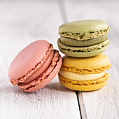 Colorful macaroons stacked in pile against wooden white surface