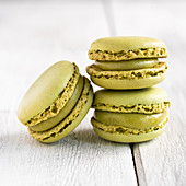 Green macaroons stacked in pile against wooden white surface
