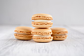 Orange macaroons stacked in pile against wooden white surface