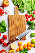 Fresh vegetables, salad leaves and greens and cutting board with chefs knife