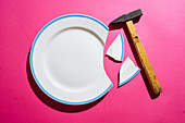 Broken white plate on pink background with hammer