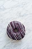 Donut mit Schokoladenglasur auf Marmorhintergrund