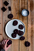 Hand grabbing cookies covered with chocolate syrup in white plate on wooden table