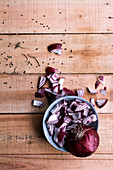 Raw chopped red onion in bowl and on rustic wooden table