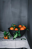 Orange tangerines in ceramic ornamental bowl on table