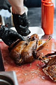 Male in gloves cutting fried chicken on wooden table in market stall