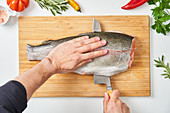 Hands cutting raw fish with knife on wooden board with fresh herbs peppers and species