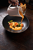 Hand of chef pouring dish with red fish and green herbs with orange sauce in stylish black bowl