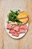 Ham with slices of roasted bread and fresh arugula in white plate on wooden table