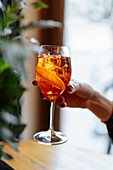 Woman holding alcohol cocktail with aperol and campari decorated with slices of orange