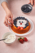 Woman decorated homemade cake with blueberry and strawberry with bowl of sour cream