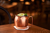 Moscow Mule served in copper mug decorated with lemon slice on wooden table