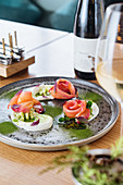 Salmon rolls with onion and herbs on metal plate with glass and bottle of white wine