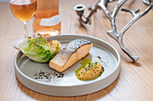 Steamed salmon served with grilled cabbage on white ceramic plate on wooden table